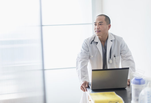 Korean doctor standing near laptop in office