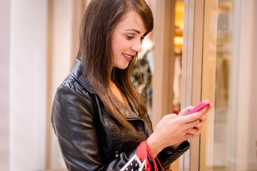 Beautiful woman using a mobile phone outside a shop