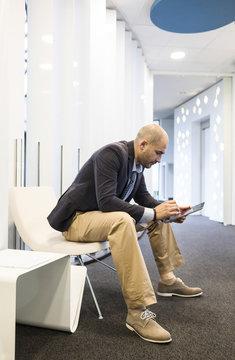 Caucasian businessman using digital tablet in office lobby