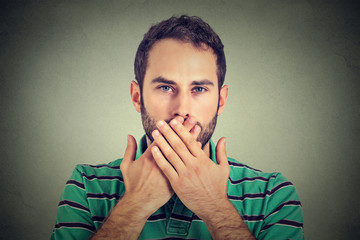 man with hands over his mouth, speechless isolated on gray wall background