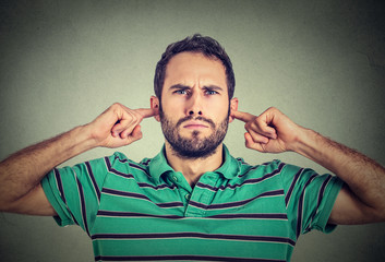 headshot displeased young man plugging ears with fingers doesn't want to listen