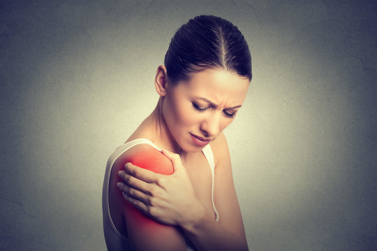 Injured joint. Woman patient in pain having painful shoulder colored in red