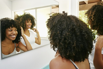 Mixed race women admiring themselves in mirror