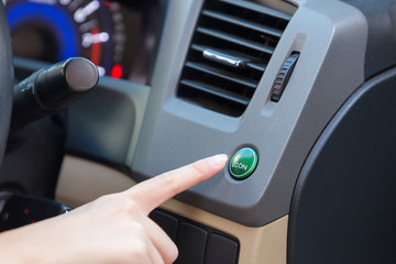 Hand finger press button eco mode inside car.