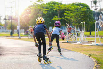 Young couples roller skates outdoor in park.