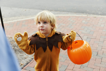 Caucasian boy in lion costume trick or treating on Halloween
