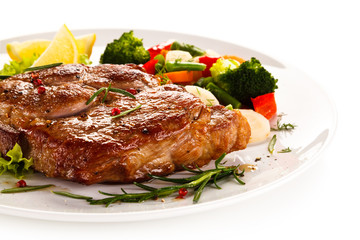 Grilled steak and vegetables on white background