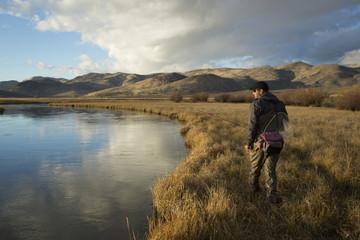 Man carrying fishing supplies near river