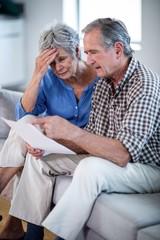 Worried senior couple checking the bills