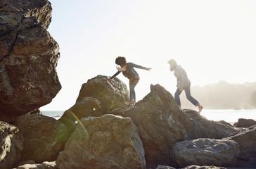 Couple climbing on boulders on beach
