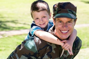 Happy soldier giving piggyback to his son