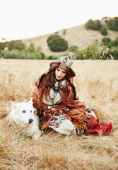 Nomadic Caucasian woman sitting in grass with wolf