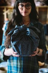Mixed race woman holding wrapped gift