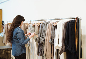 Mixed race business owner arranging clothing in store