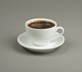 Cup of coffee and saucer on a gray background.