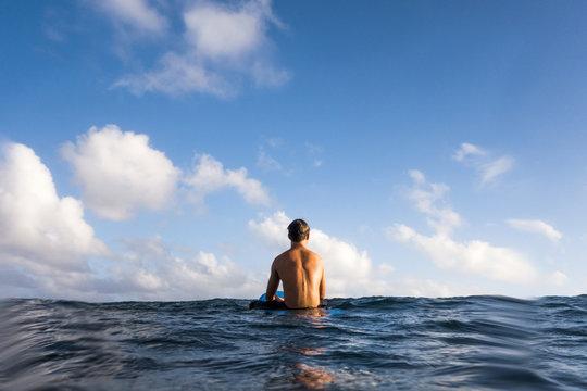 Rear view of surfer sitting on surfboard in ocean