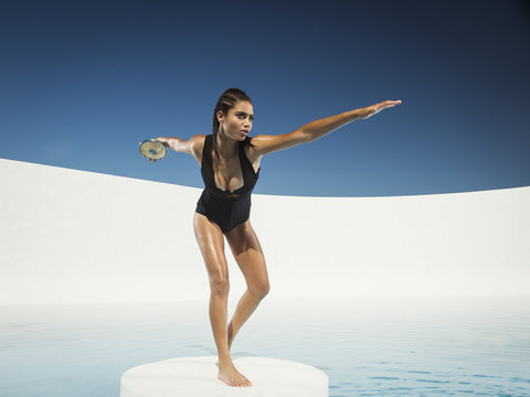 Mixed race woman on ice floe throwing discus