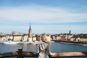 girl is standing back with a view of the city of Stockholm