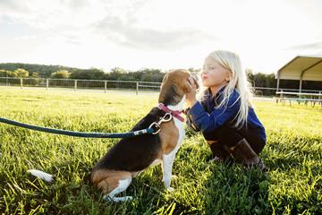 Caucasian girl kissing puppy on farm