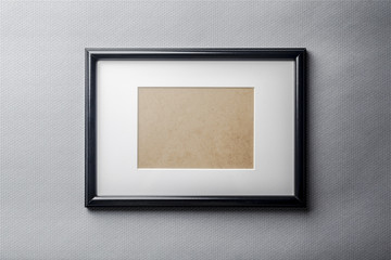 Black plain empty thin wood picture frame with white mat passe-partout on grey bricks background