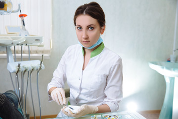 Dentist woman with medical instruments in the dental office doing procedures