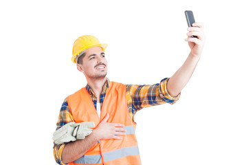 Cheerful engineer with yellow helmet taking a selfie
