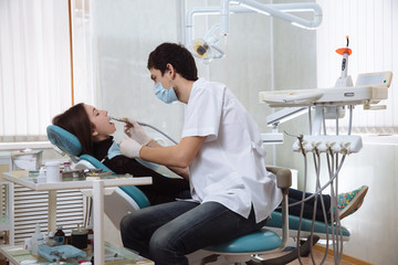 Dentist man making procedures with his patient in dental office