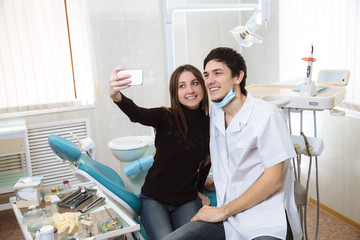 Dentist man with his patient doing photo selfie in dental office