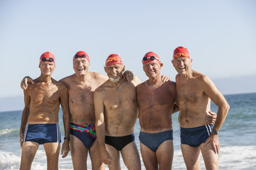 Older men on swimming team smiling on beach