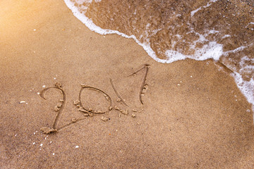 Inscription written in the wet beach sand being washed with sea water wave. Time passing away or New Year celebrating concept.