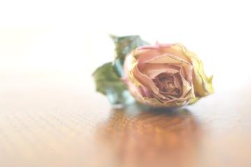 Bellissima rosa appassita appoggiata su un piano di legno