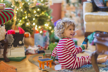 Caucasian baby boy opening presents near Christmas tree