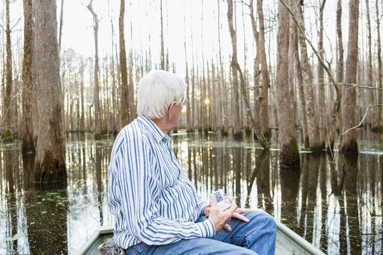 Older Caucasian man riding boat in swamp