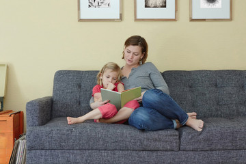 Caucasian mother reading to daughter on sofa