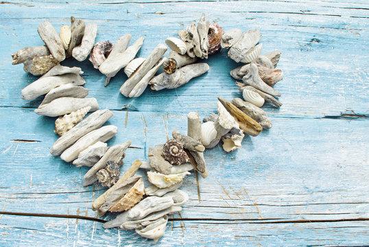 Maritime Urlaubserinnerung: Herz aus Muscheln und Strandgut auf blauem Holz :)