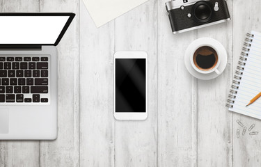 White smart phone with isolated screen for mockup on office desk. Laptop, camera, cup of coffee, paper, notepad, pencil on white table. Top view.