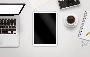 White tablet with isolated screen for mockup on office desk. Laptop, camera, cup of coffee, paper, notepad, pencil on white table. Top view.