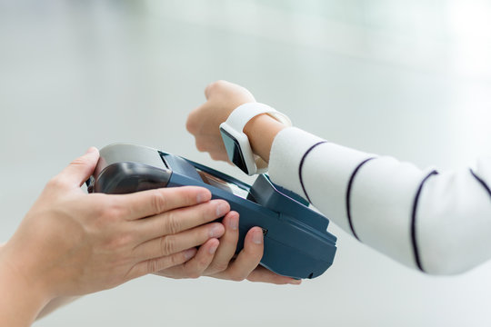 Woman paying by smartwatch with NFC technology