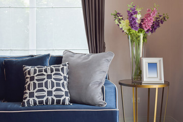 Navy blue modern classic sofa and retro, gray and blue pillows with a lovely orchid vase on side table in living corner
