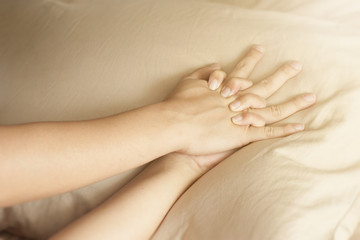 Close up hands of a couple having sex on a bed