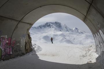 Túnel con un fondo de montañas y mujer esquiadora