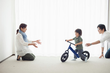 Parents with son learning to ride bicycle