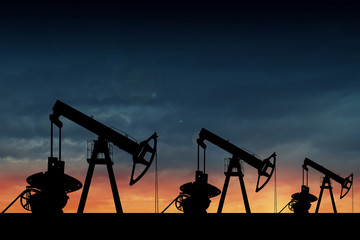 Silhouette of three oil pumps at sunset.