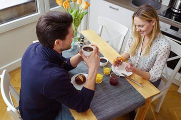 junges paar sitzt in der küche beim frühstück