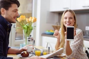 lachende frau sitzt am frühstückstisch und zeigt ihr handy-display