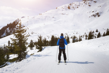 Skier skiing on easy blue trail with beautiful landscape