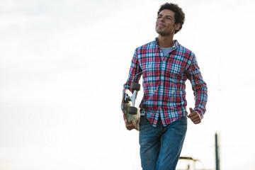 Skateboarder walking with skateboard in hand