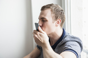 Man kissing mobile phone