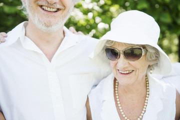 Portrait of senior woman wearing sunglasses and white sunhat