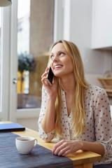 junge frau sitzt am küchentisch und telefoniert mit ihrem handy